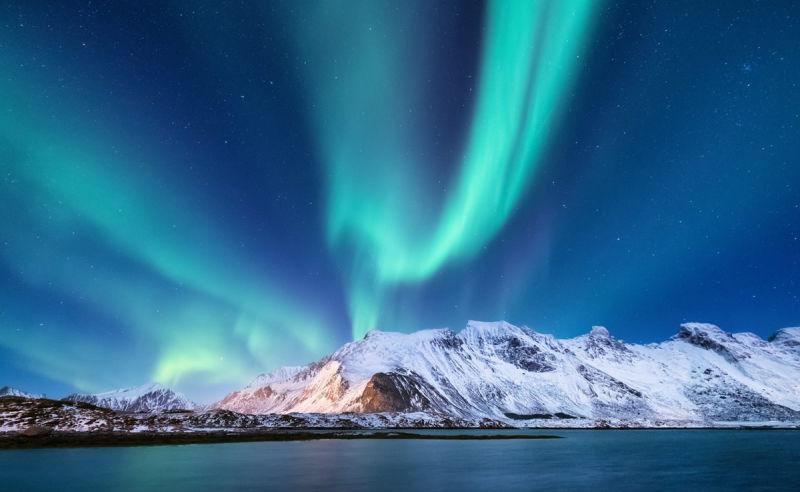 Nordlichter über verschneiten Bergen in Finnland