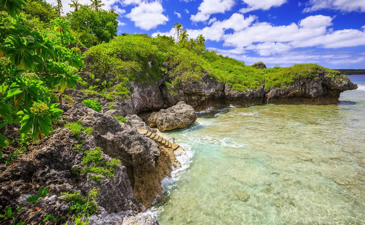 Meer und prächtig grüner Fauna am Strand von Niue